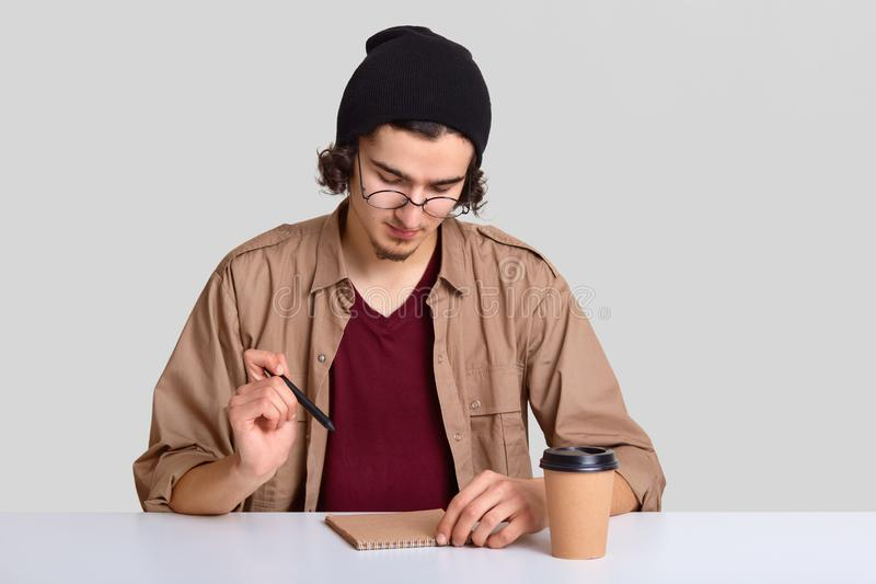 Photo of stylish guy has long curly hair, wears black hat and casual shirt, focused into notebook, makes list to do, sits at white stock image