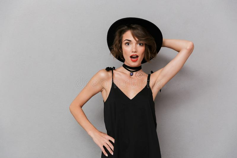 Photo of stylish woman 20s wearing black dress and hat smiling a royalty free stock photo