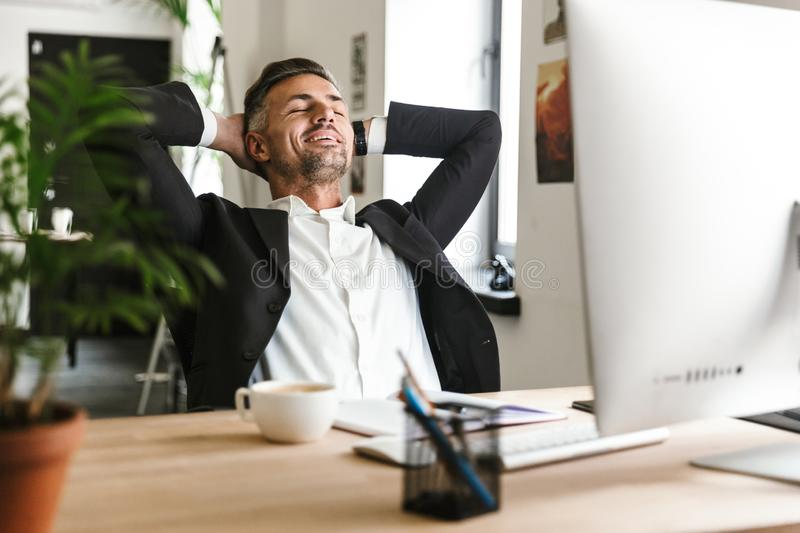 Photo of successful businessman smiling while sitting at desk and working on computer in office royalty free stock photography
