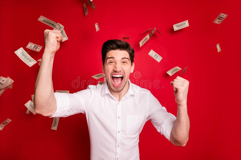 Photo of successful champion winning man standing in rain of currency bucks banknotes while isolated with red background. Photo of successful champion, winning royalty free stock photography