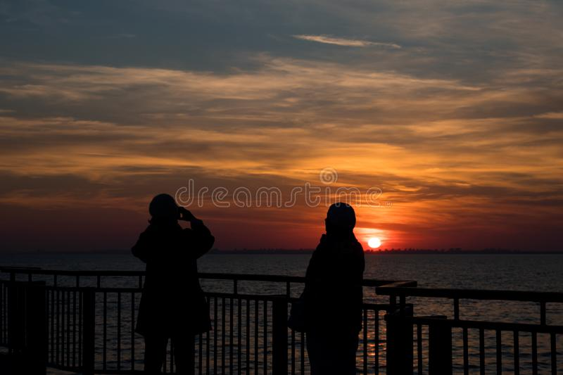 Photo of the sunset with the silhouette of a two ladies. A beautiful sunset over Black Sea. On this photo you can see a silhouette of two ladies enyoying the stock photography