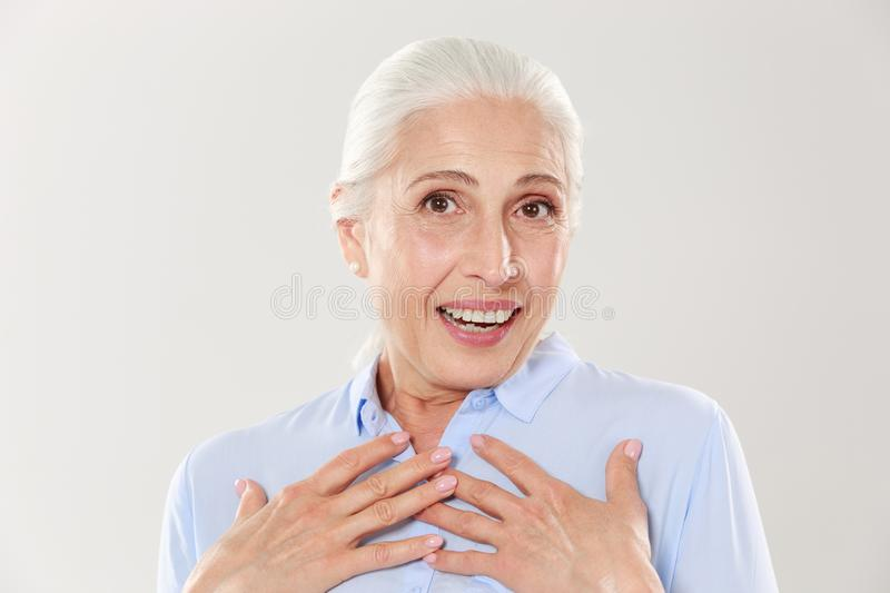 Photo of surprised old lady with hands on her chest, looking at. Camera, isolated over white background stock photography