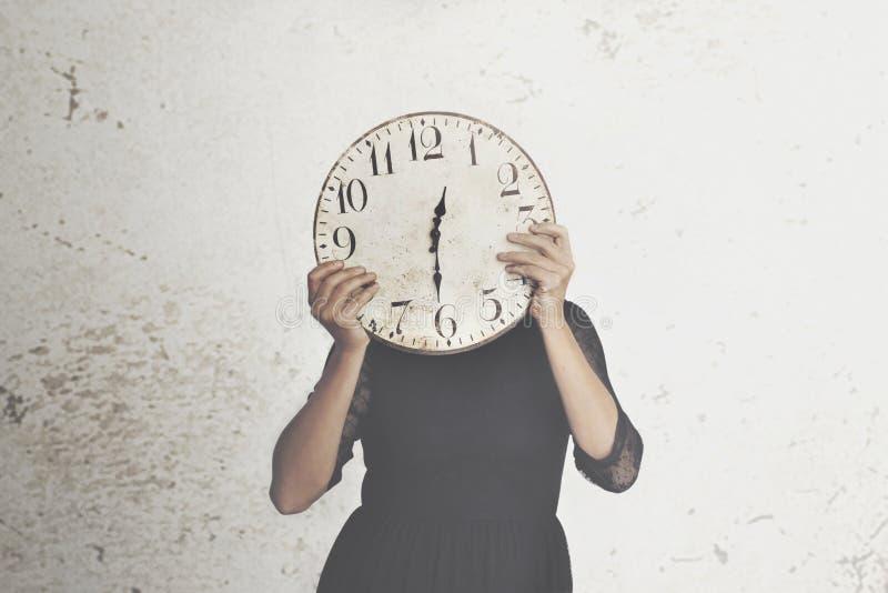Photo surréaliste d'une femme se cachant derrière une grande horloge photographie stock