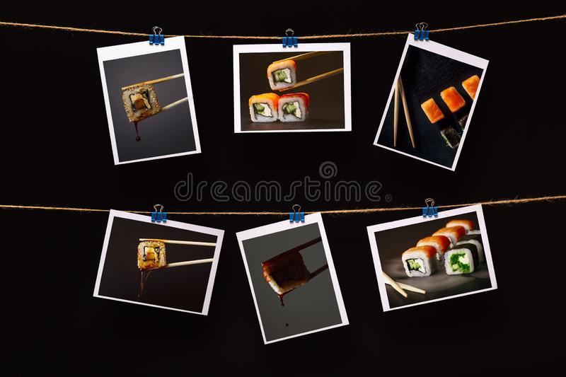 Photo of sushi with fish attached with on linen rope on a black background, concept japanese food industry, snack bar decor royalty free stock photos