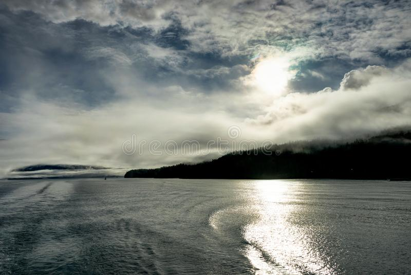 Mountains covered in clouds on a misty morning on the Ferry towa. Photo taken in Alaska, United States of America stock photography