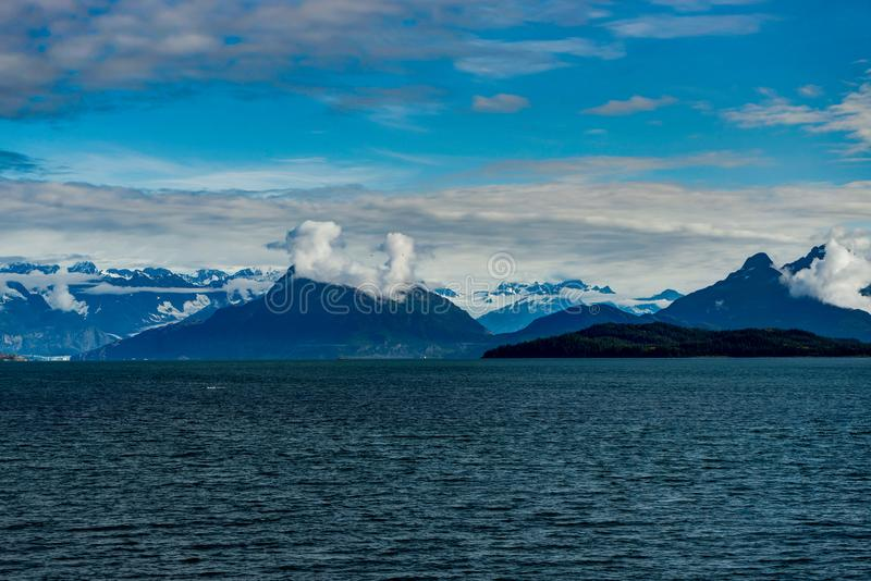 Mountains covered in clouds on a misty morning on the Ferry towa. Photo taken in Alaska, United States of America royalty free stock photos