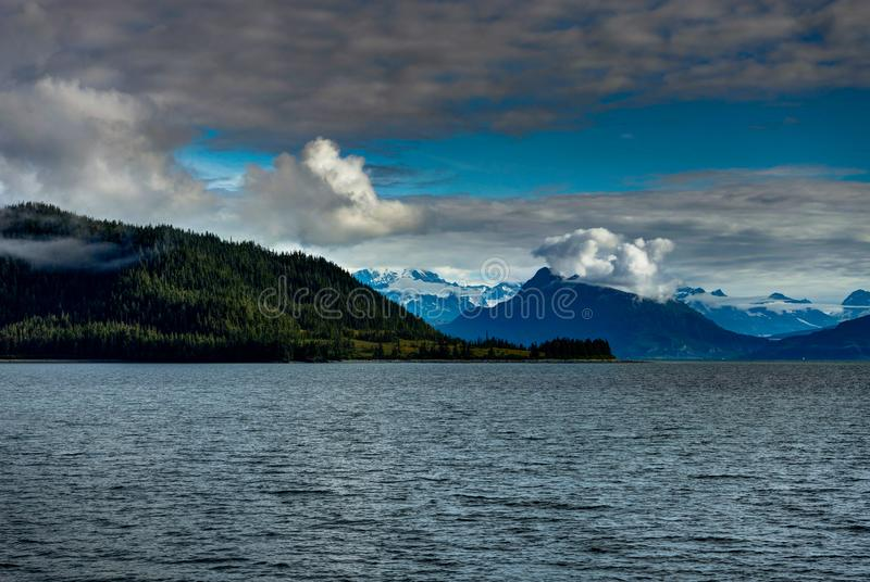 Mountains covered in clouds on a misty morning on the Ferry towa. Photo taken in Alaska, United States of America royalty free stock image