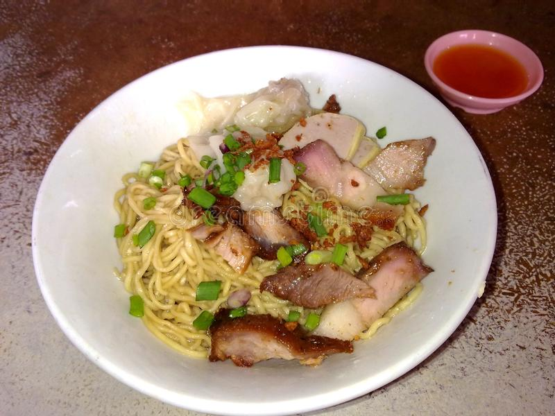 A bowl of roasted pork dumpling noodles with chilli sauce royalty free stock photo