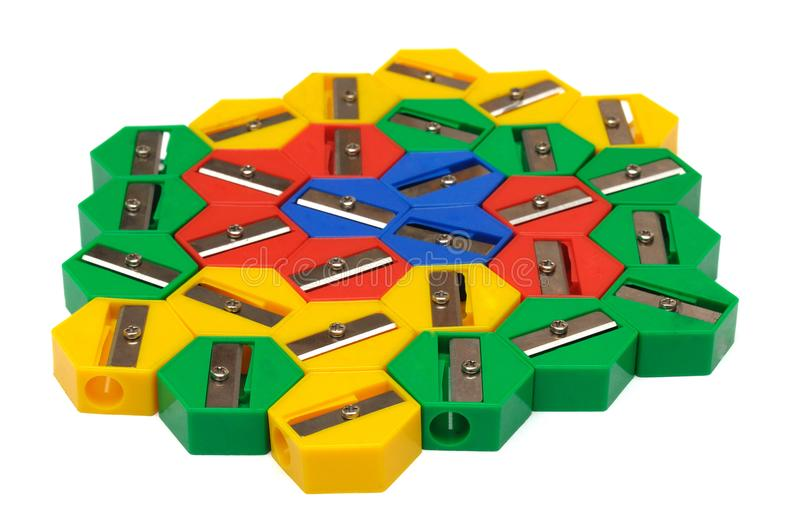 A bunch of multiple colored pencil sharpeners. A photo taken on a bunch of multiple colored hexagonal shaped pencil sharpeners against a white backdrop royalty free stock photos