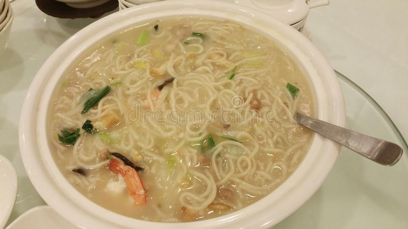 A large bowl serving of asian prawn noodles on a table royalty free stock photos
