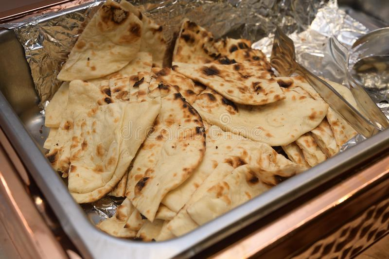 A large open tray of Indian Naan leavened oven baked flatbread royalty free stock image