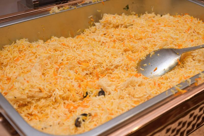 A large tray of Biryani fried mixed rice dish with a spoon scoop ladle stock photography