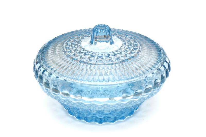 A light blue tableware covered glass bowl. A photo taken on a light blue tableware covered crystal glass bowl against a white backdrop stock photography