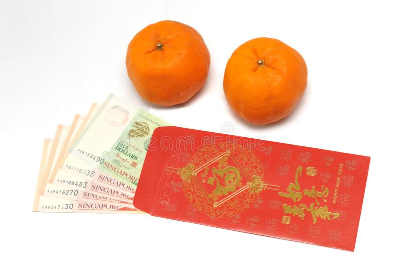 A pair of mandarin oranges and a red envelope with Singapore money notes inside stock photography