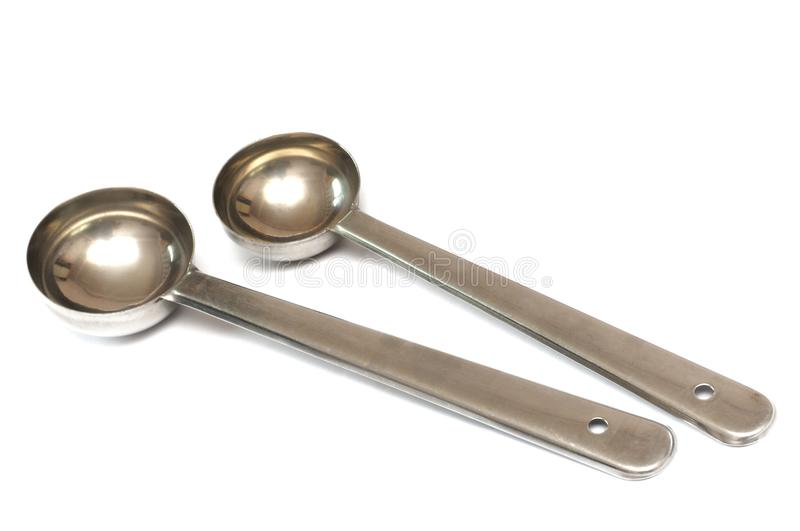 Stainless steel measuring sugar coffee tea oil spoon scoops. A photo taken on a pair of stainless steel measuring sugar coffee tea oil spoon scoops against a royalty free stock images