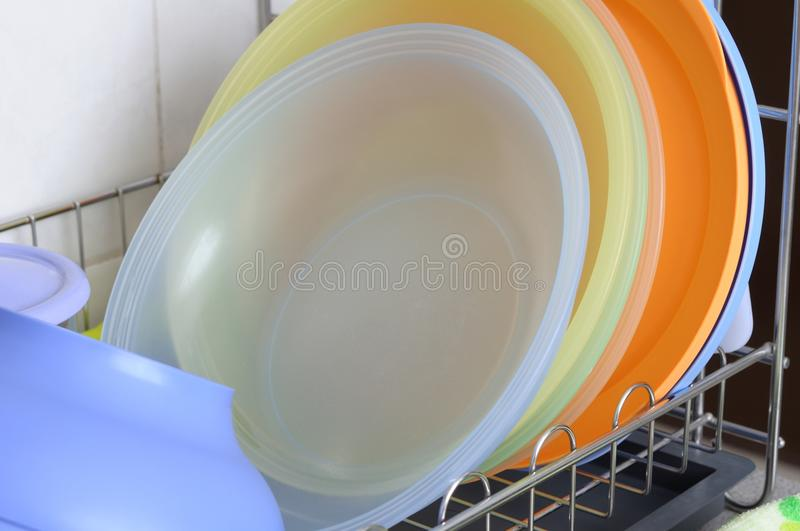 Some plastic plates on a dish dryer rack. A photo taken on some colorful plastic plates left to dry on a stainless steel dish dryer rack at a kitchen stock photography