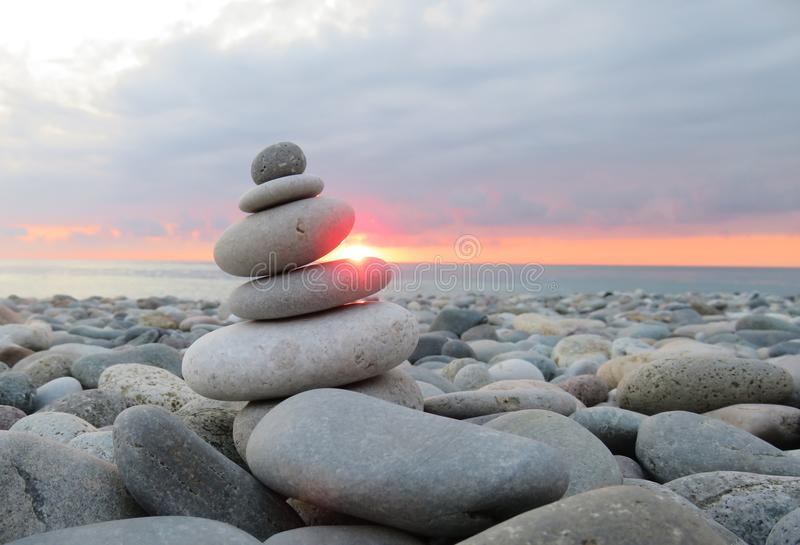 Photo taken in summer. Pyramid of stones against the background. Pyramid of stones against the background of the sea and sunset stock photo