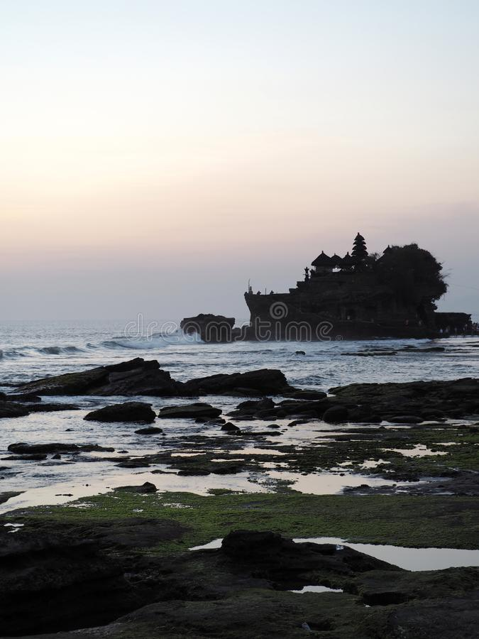 The famous temple Tanah Lot built on a built on a rocky island in the middle of the water at sunset in Bal, Indonesia. Photo taken at sunset in August 2018 royalty free stock images