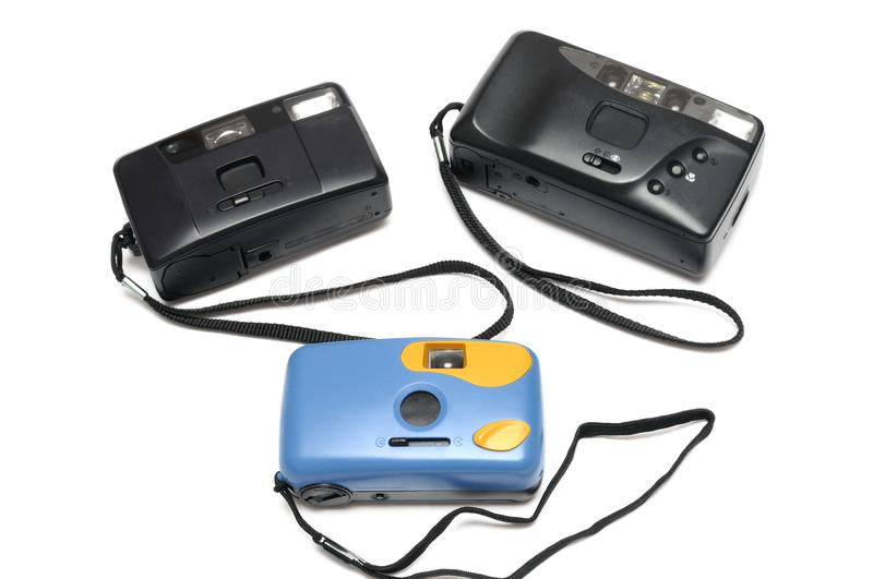 Three film cameras with black wrists straps. Two are black while the other is blue in color. royalty free stock photography