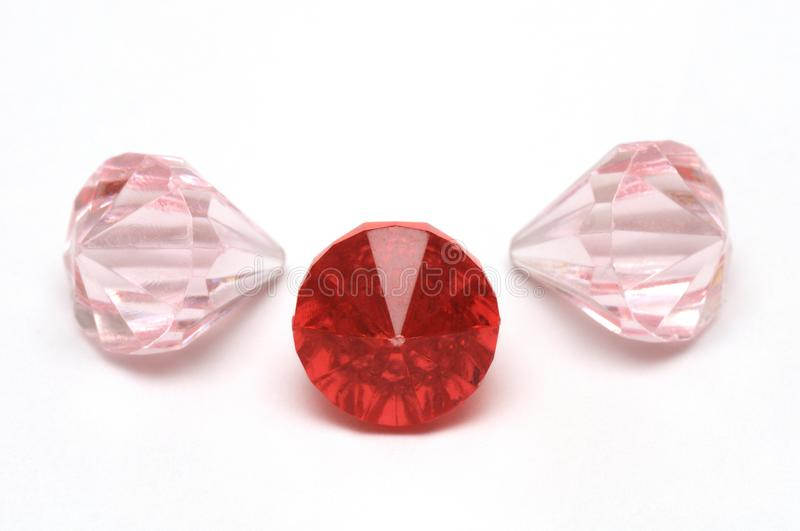 Three ruby red and light pink colored fake diamonds royalty free stock image