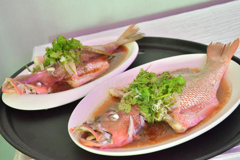 Two plates of cooked steamed fish dishes set for serving as in an Asian restaurant stock images