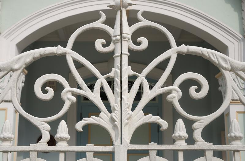A white painted wrought iron gate with intertwining vines design stock photos