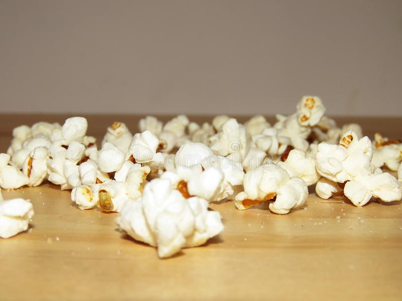 Salty popcorn spilled on the table stock photography