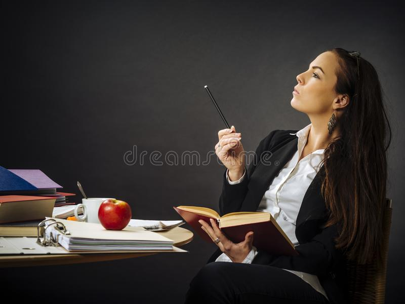 Beautiful teacher sitting at her desk thinking royalty free stock photography