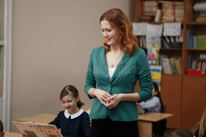 Photo of teacher writing sum on blackboard and looking at pretty pupil near by stock photography