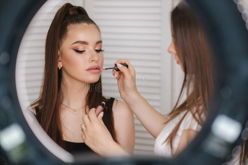 Photo though the ring lamp of makeup artist doing a makeup for attractive young girl. Background of white folding screen stock photo