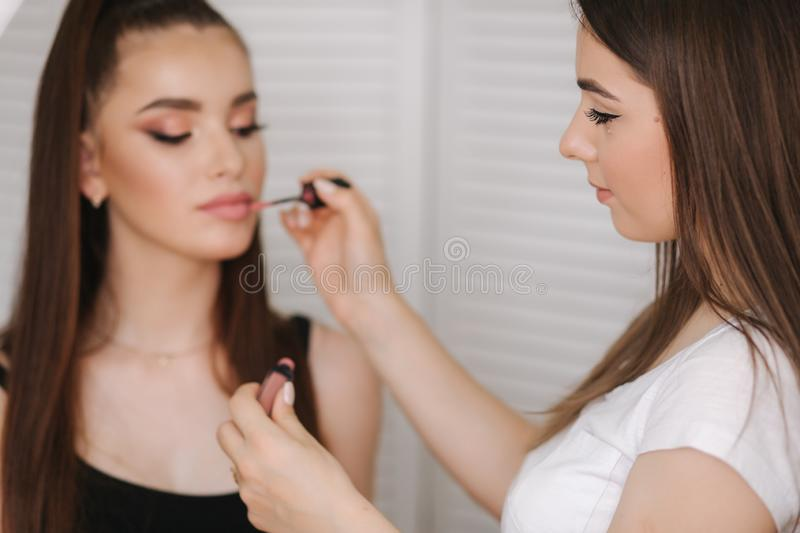 Photo though the ring lamp of makeup artist doing a makeup for attractive young girl. Background of white folding screen stock photos