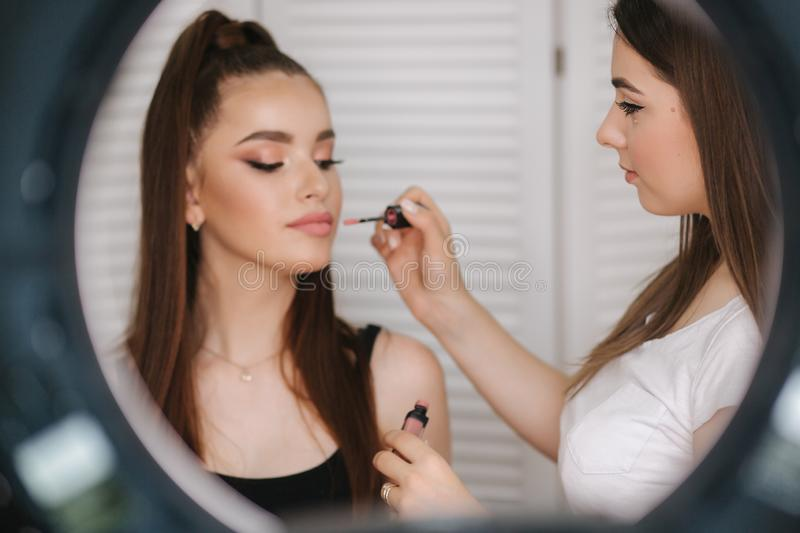 Photo though the ring lamp of makeup artist doing a makeup for attractive young girl. Background of white folding screen royalty free stock photo