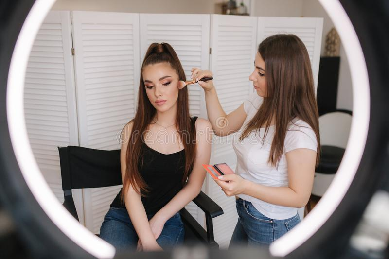 Photo though the ring lamp of makeup artist making a makeup for attractive young girl. Background of white folding royalty free stock photos