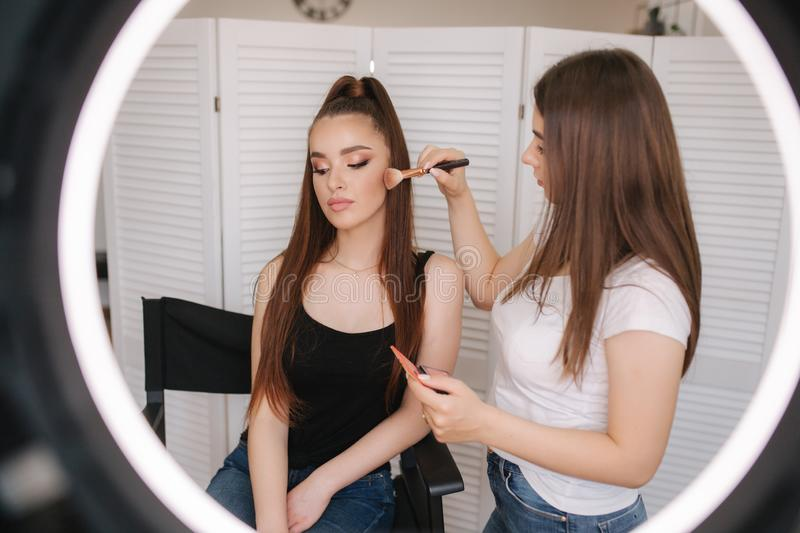 Photo though the ring lamp of makeup artist making a makeup for attractive young girl. Background of white folding stock image