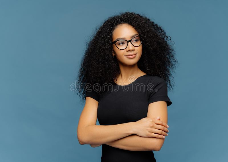 Photo of thoughtful satisfied Afro woman keeps hands crossed over chest, focused aside, wears transparent glasses, casual black t stock photo