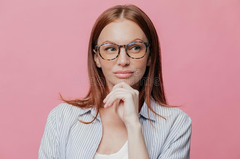 Photo of thoughtful woman has serious expression, keeps hand on chin, wears glasses and elegant shirt, isolated over pink royalty free stock image