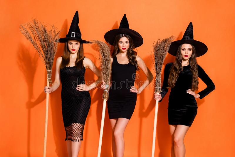 Photo of three cruel witch ladies holding brooms in hands waiting full moon for flying wear black dresses and wizard. Photo of three cruel witch ladies holding stock photos