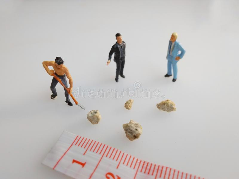 Three mini figure toys arround very small kidney stones top view royalty free stock images