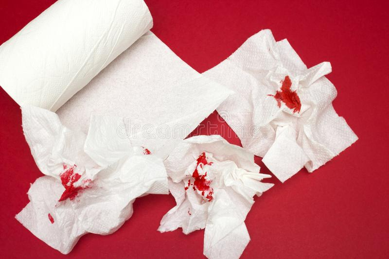 A photo of three used bloody toilet paper and toilet paper roll on the red background. Menstrual, hemorrhoids bleeding. Bloo. A photo of three used bloody toilet stock images