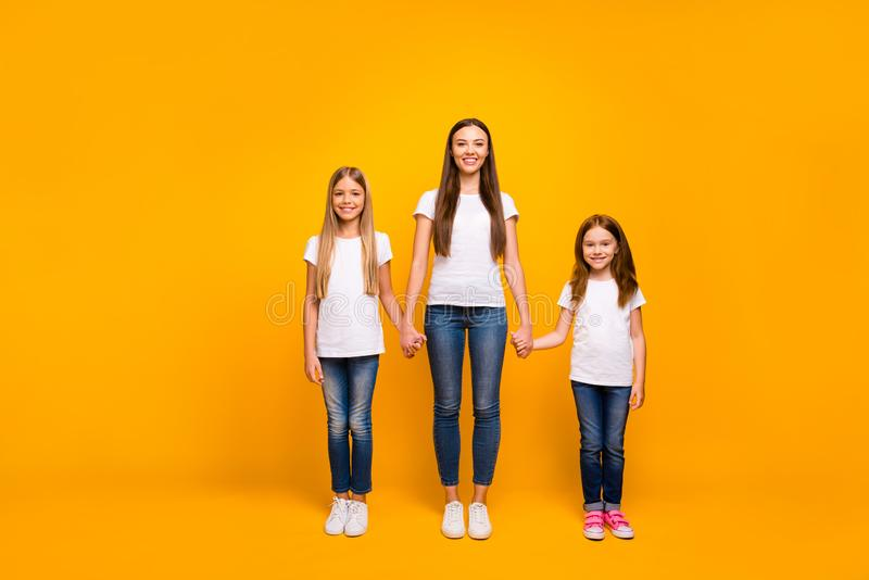 Photo of three sister ladies holding arms glad to be together at weekend wear casual outfit isolated yellow background stock photography