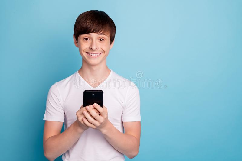 Photo of tight smiling boy taking smartphone with his own hands for first time while isolated with blue background royalty free stock photo