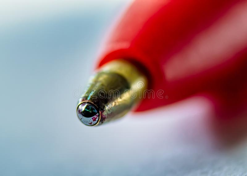 Tip of red ballpoint pen in extreme closeup royalty free stock photo