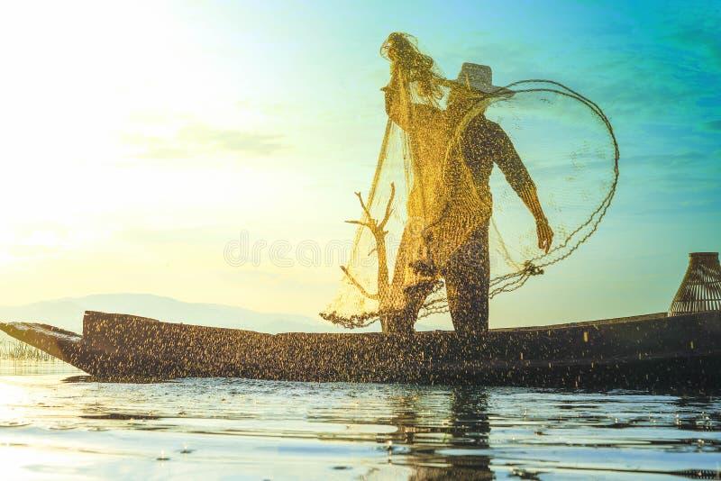 Photo tirée de l'éclaboussure de l'eau du pêcheur tout en jetant le fishin images libres de droits
