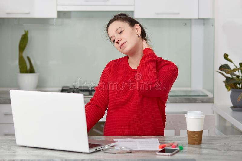 Photo of tired European woman keeps hand on neck, works freelance at laptop computer, wears red sweater, anticipates for baby,. Poses against kitchen interior royalty free stock photo