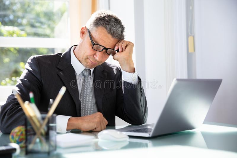 Businessman Sleeping In Office. Photo Of Tired Mature Businessman Sleeping In Office royalty free stock images