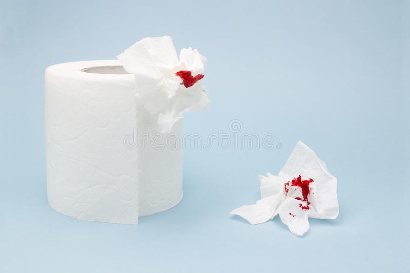 A photo of a toilet paper roll and two used bloody toilet paper sheets. Blood drops and traces. Menstrual or hemorrhoids bleeding. A photo of a toilet paper royalty free stock image