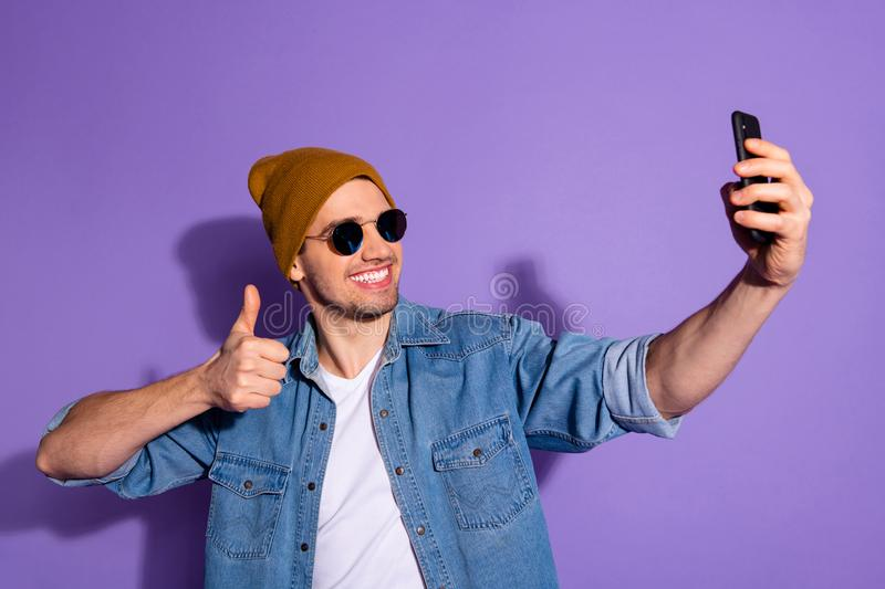 Photo of toothy cheerful attractive youngster blogger giving positive feedback by video call on telephone taking selfie stock images