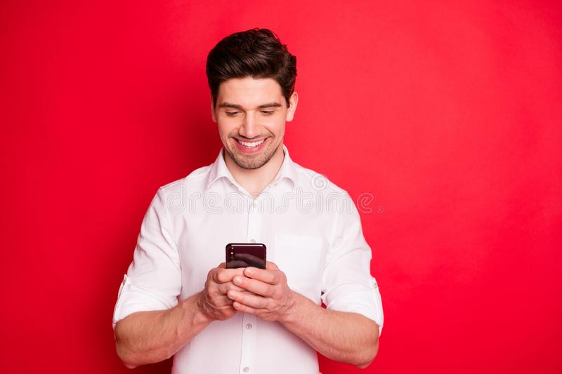 Photo of toothy smiling modern man typing message to someone with his telephone while isolated with red background. Photo of toothy smiling, modern man typing stock photo