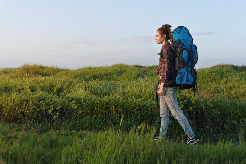 Beautiful traveler woman walking in the meadow with trekking backpack. Photo of traveling alone woman walking in the meadow with trekking backpack. Photo taken royalty free stock photo