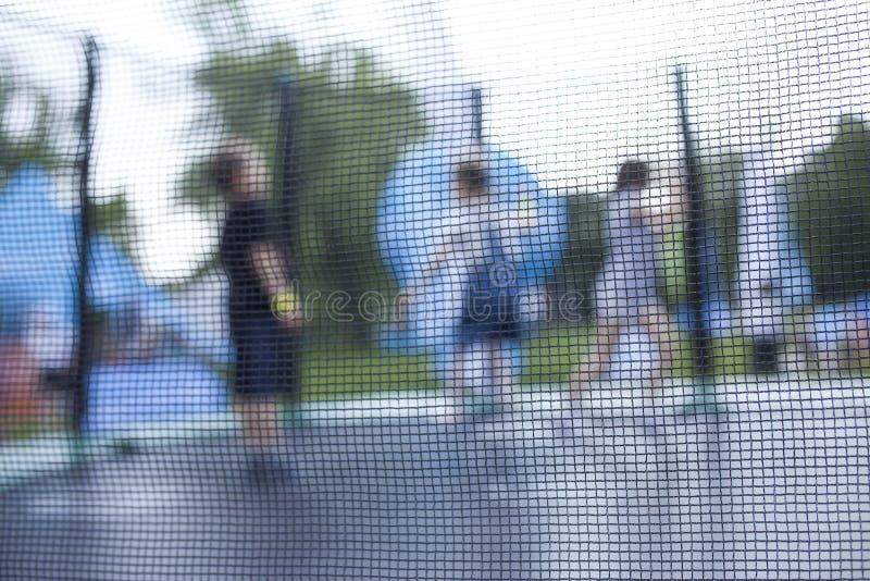 Photo trouble des enfants ayant l'amusement sur un trempoline image stock